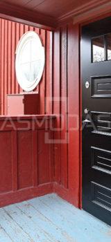 Lauko durys - šarvuotos, tamsiai rudos spalvos, su stačiakampiais ir langeliais.